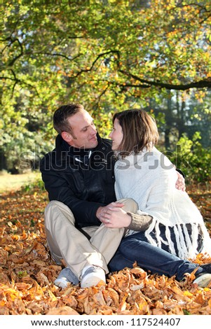 Romantic young couple sitting in a close embrace gazing amorously into each others eyes while seated amongst fallen autumn leaves in a forest - stock photo