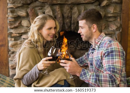 Romantic young couple toasting wineglasses in front of lit fireplace - stock photo