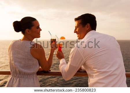 romantic young couple toasting with cocktail on cruise ship - stock photo