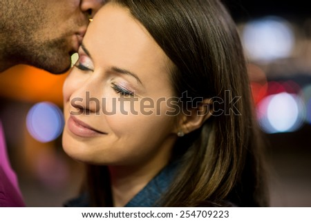 Romantic young couple together on date in street at night - stock photo