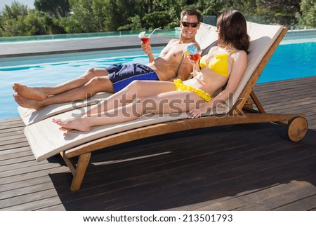 Romantic young couple with drinks sitting by swimming pool - stock photo