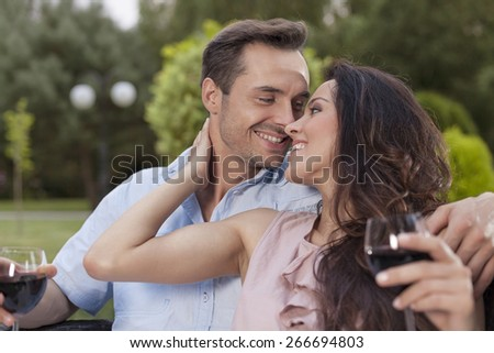 Romantic young couple with wine glasses in park - stock photo