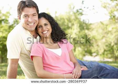 Romantic Young Hispanic Couple Relaxing In Park - stock photo
