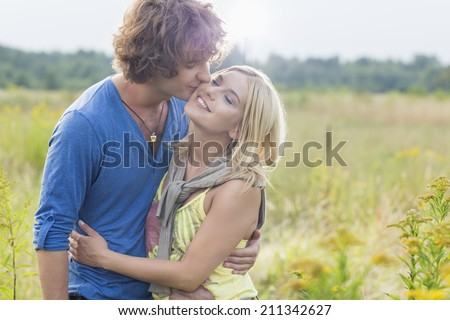 Romantic young man kissing woman in field - stock photo
