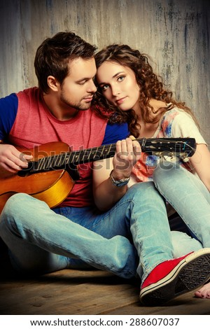 Romantic young man playing the guitar to his beloved girl. Happiness. Love concept. - stock photo