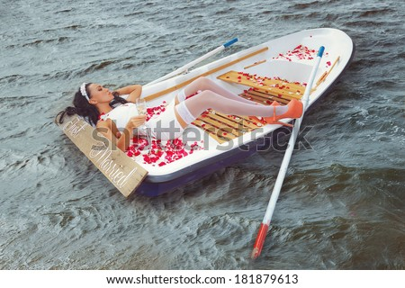 Romantic young Woman cuddling in rowboat at lake - stock photo