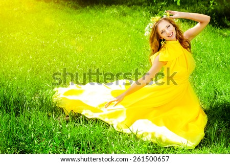 Romantic young woman in beautiful yellow dress sitting on a green lawn in the garden.  - stock photo