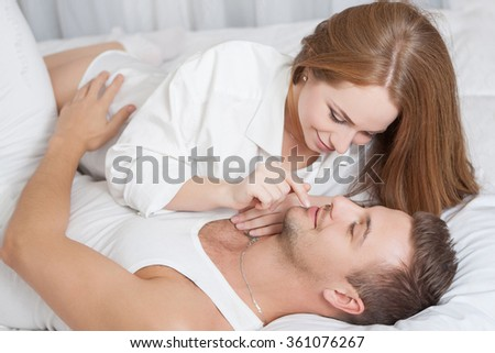 Romantic young woman touching man's lips while lying in bed - stock photo