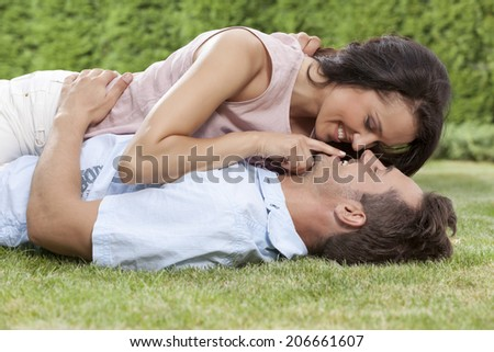 Romantic young woman touching man's lips while lying on him in park - stock photo