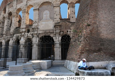 ROME - APRIL 29:Italian man work on his laptop outside the Colosseum on April 29 2011 in Rome Italy.The Colosseum in Italy only took 9 years to build using over 60,000 Jewish slaves.  - stock photo