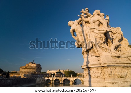 ROME - APRIL 17, 2013: Massive allegorical travertine sculptural groups on the bridge Ponte Vittorio Emanuele II and Ponte Sant'Angelo. Mausoleum of Hadrian (Castel Sant'Angelo). Rome, Italy. - stock photo