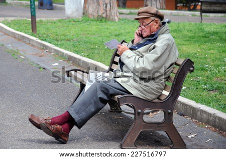 ROME, ITALY - APRIL 30, 2014: Old man sits on the bench in the park with a newspaper on his lap and speaks on the cell phone - stock photo