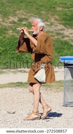 ROME, ITALY - APRIL 21, 2015:  Rome Foundation Anniversary historical reconstruction, senior man plays piffero old Italian Fife - stock photo