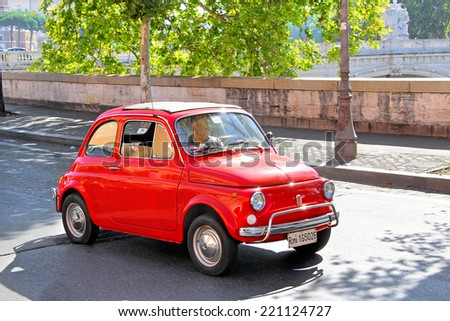 ROME, ITALY - AUGUST 1, 2014: Red tiny car Fiat 500 at the city street. - stock photo
