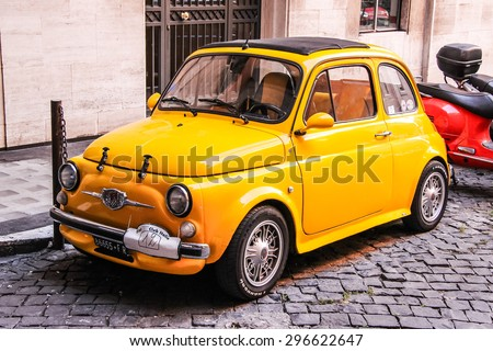 ROME, ITALY - AUGUST 1, 2014: Yellow tiny retro car Fiat 500 at the city street. - stock photo