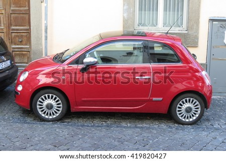 ROME, ITALY - CIRCA OCTOBER 2015: red FIAT 500 car (new version) parked in a street of the city centre - stock photo