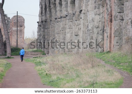 ROME, ITALY - FEBRUARY 26 , 2015: man walking along the ancient ruins of the Roman aqueduct at the Parco degli Acquedotti public park - stock photo