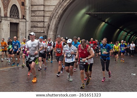 Rome, Italy - March 23, 2014:  Rome Marathon. The participants in the Rome Marathon make their way to the finish line, visibly tired from the 40 km race. - stock photo