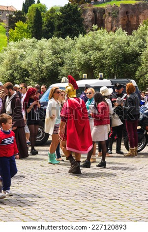 ROME, ITALY - MAY 03, 2014: Actor depicting a Roman legionary for tourists near the Colosseum. Rome, Italy - stock photo
