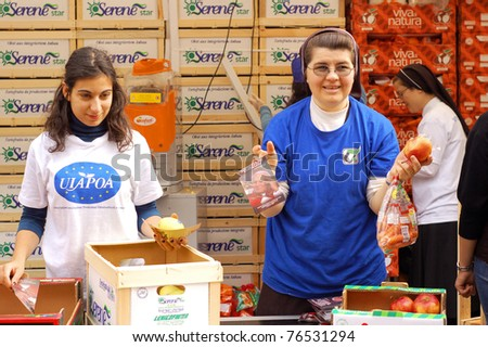 ROME, ITALY - MAY 1: Female volunteers hand out snacks to people attending the beatification of Pope John Paul II in Rome, Italy on May 1, 2011. - stock photo