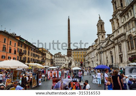Rome  May 6 2015: Tourists visiting the Fontana dei Quattro Fiumi meaning Fountain of the Four Rivers and artists selling paintings in Piazza Navona. Rome, Italy - stock photo