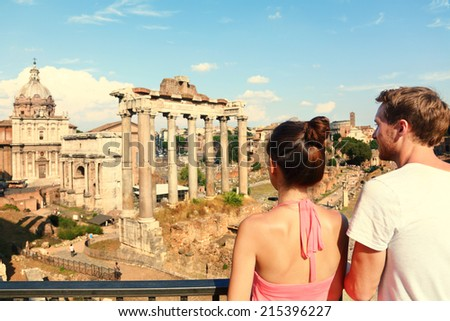 Rome tourists looking at Roman Forum landmark in Rome. Couple sightseeing on travel vacation in Rome, Italy. Happy tourist couple, man and woman traveling on holidays in Europe. - stock photo