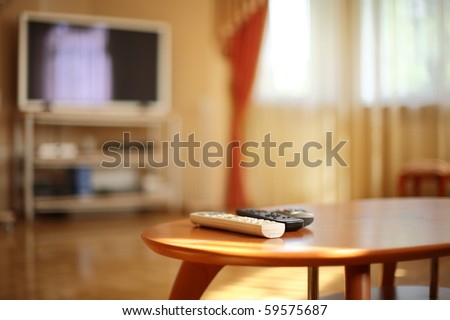 Romote controls on wooden table, tv in the background. Shallow DOF, focus on white remote. - stock photo
