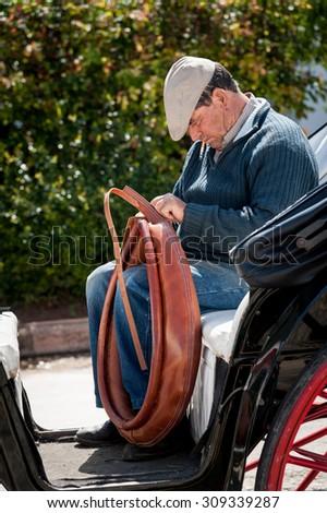 RONDA, SPAIN - MAY 21, 2012: A coachman repairing a traditional horse collar in Ronda, Andalucia,  Spain. - stock photo