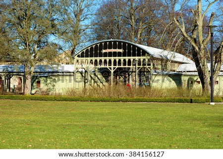Ronneby, Sweden - February 26, 2016: The Brunnshallen is a heritage listed building from 1897, built to shelter outdoor leisure activities. Rose garden in front of building and person partly visible. - stock photo