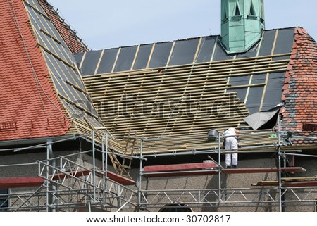 Roof construction works. Worker and scaffolding. Building renovation. - stock photo
