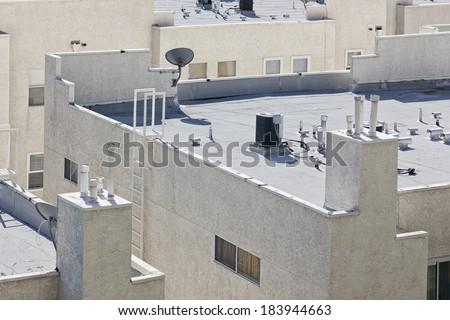 Roof is flat with air conditioners on top of a modern apartment. - stock photo