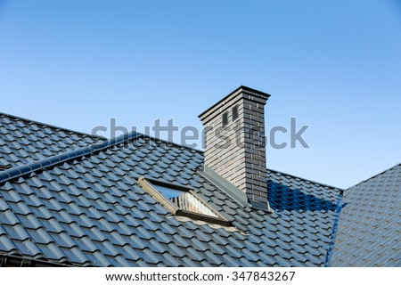 Roof of a detached house with a skylight and chimney against the sky - stock photo