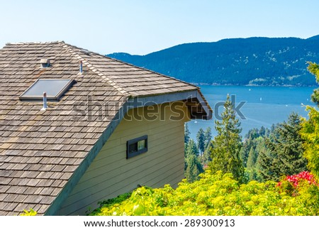 Roof of a modern house facing ocean inlet in great neighborhood, in suburbs of Vancouver, Canada. - stock photo