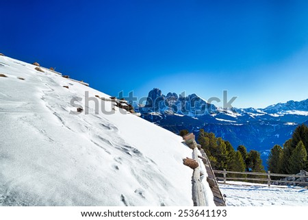 Roof of alpine chalet surrounded by a fence in the snow in front of a panorama of snowy peaks on a bright sunny day in winter on Dolomites Alps - stock photo