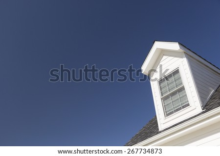 Roof of House and Windows Against Beautiful Deep Blue Sky. - stock photo
