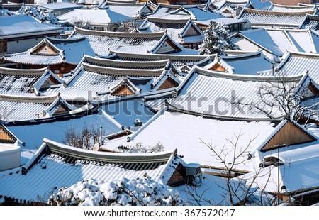 Roof of Jeonju traditional Korean village covered with snow, Jeonju Hanok village in winter, South Korea. - stock photo