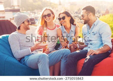 Roof party with friends. Four young cheerful people chatting and drinking beer while sitting at the bean bags on the roof of the building - stock photo