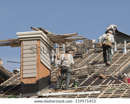 Roof repairs of an apartment building in Colorado. - stock photo
