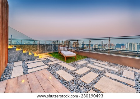 Roof terrace with jacuzzi and sun lounger during twilight  - stock photo