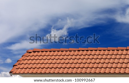 Roof tiles and blue sky with clouds - stock photo