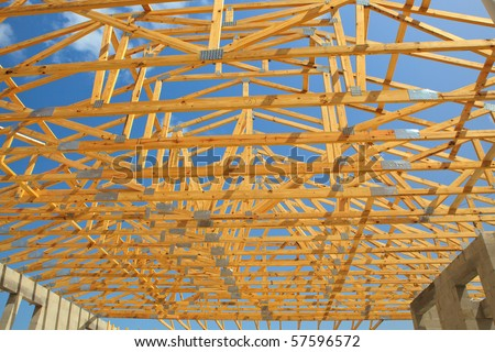 Roof trusses sitting a cement block walls view from inside home. Blue sky with clouds in background - stock photo