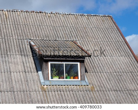 Roof window of old house with asbestos sheet roof.       - stock photo