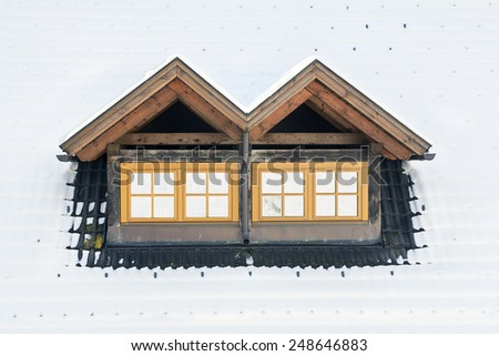 Roof windows under snow during winter - stock photo