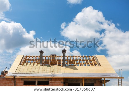 Roof with insulation and chimneys. House under construction - stock photo