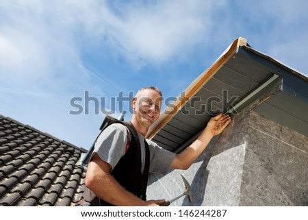 Roofer assembling parts of the dormer rooftop edge - stock photo