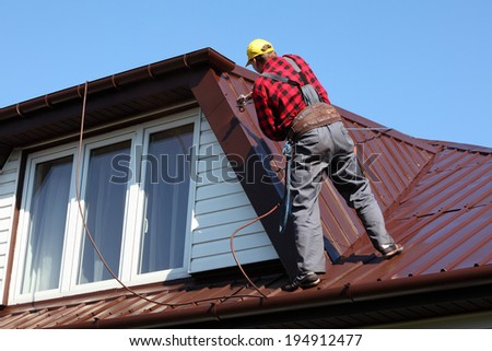 roofer builder worker with pulverizer spraying paint on metal sheet roof - stock photo