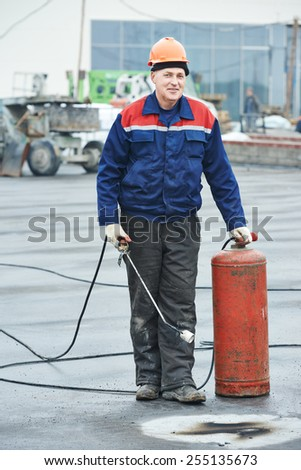 Roofer installer worker portrait at roofing felt with heating and melting of bitumen roll by torch on flame during roof repair - stock photo