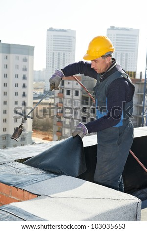 Roofer installing Roofing felt with heating and melting roll of bitumen roll by torch on flame - stock photo