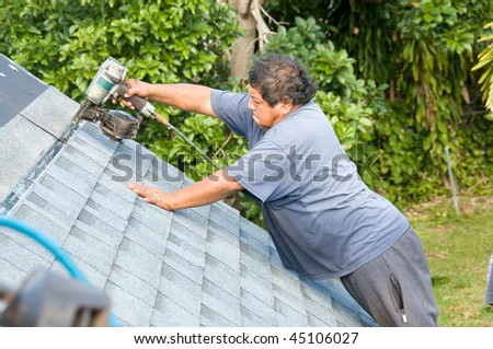 Roofer installing shingles on roof - stock photo