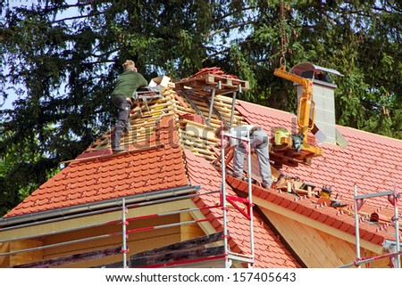 roofer on a traditional farm house in germany - stock photo
